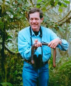 Dr Bob  holding a giant earthworm while birdwatching in Ecuador.